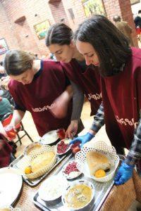 '11 alumni Nino Tetrauli, Mariam Kvaratskhelia and Nino JIbuti prepare to serve a meal at a soup kitchen and elderly house in Georgia.